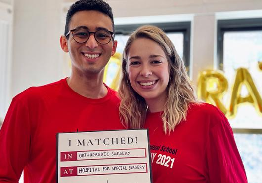 "Troy Amen with his fiancee holding ""I Matched"" sign"