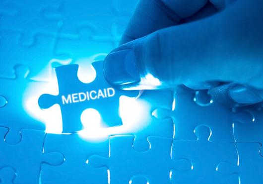 "A hand fitting a puzzle piece adorned with the word ""medicaid"" into a back-lit jigsaw puzzle."