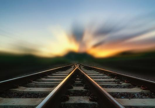 Two train tracks merge in a blurry sunset.