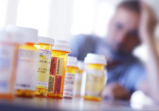A blurry man in the background behind a row of prescription drugs.