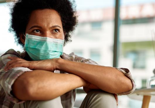 A woman wearing a surgical masks sits with her arms crossed