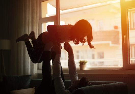 A father plays with his daughter backlit by sunset, seen through the window.