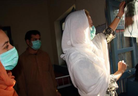 Three people in surgical masks examine an x-ray of a person's lungs.