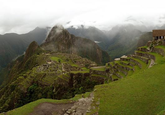 panorama of Machu Picchu site beneath cloudy skies
