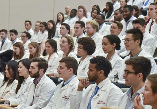 large group photo in auditorium of new students in white coats