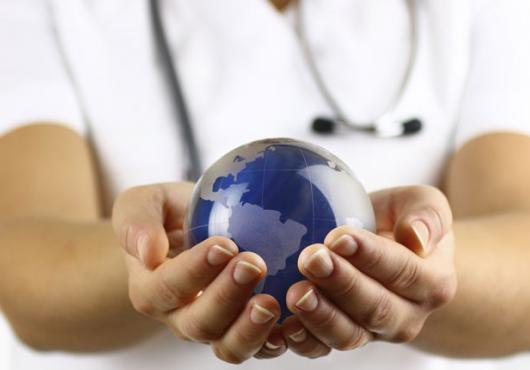 Stock image of white coated person holding a globe in hands