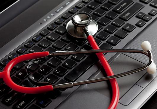 red stethoscope on laptop computer
