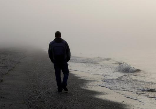 photo with silhouette of person walking on a foggy beach
