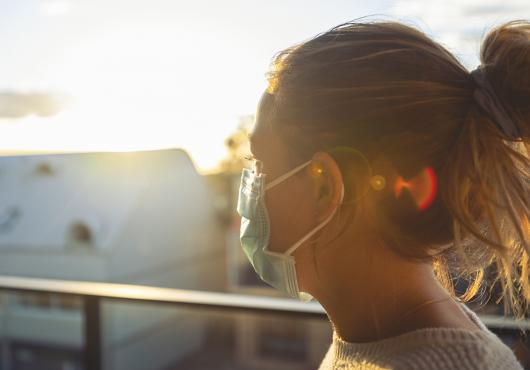 A woman  wearing a mask is seen in profile, backlit by the sun.