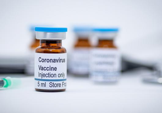 photo of vials with COVID-19 vaccine label and needle