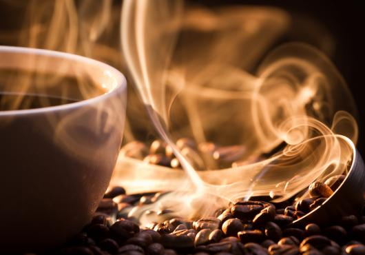 Steaming mug of coffee atop coffee beans