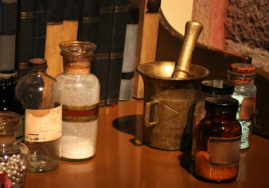 Antique medication bottles, mortar and pestle, and powders