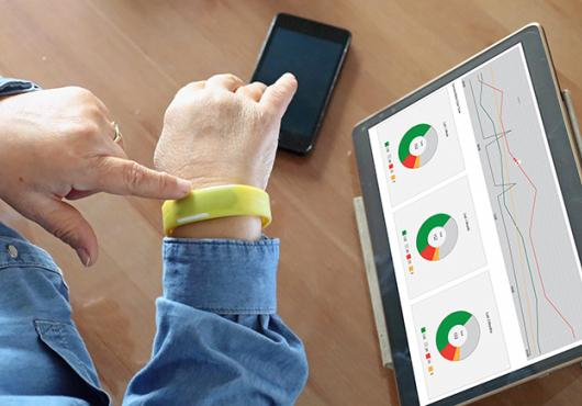 woman's wrist with smart watch and tablet with health data