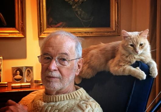 professor in sweater with cat on armchair