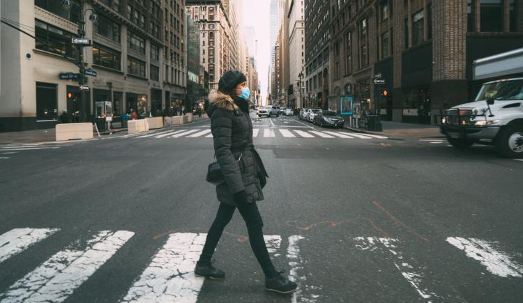 A woman in a surgical mask crossing a street in mid-town Manhattan