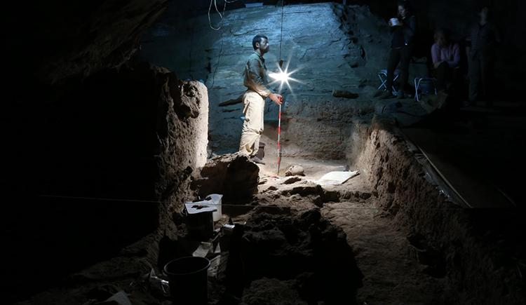 Man with lamp stands in a cave, an excavated skull in front of him