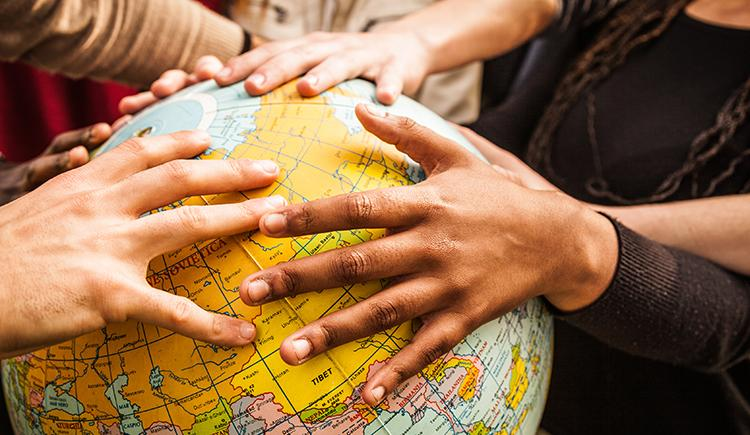 multiethnic hands on a globe