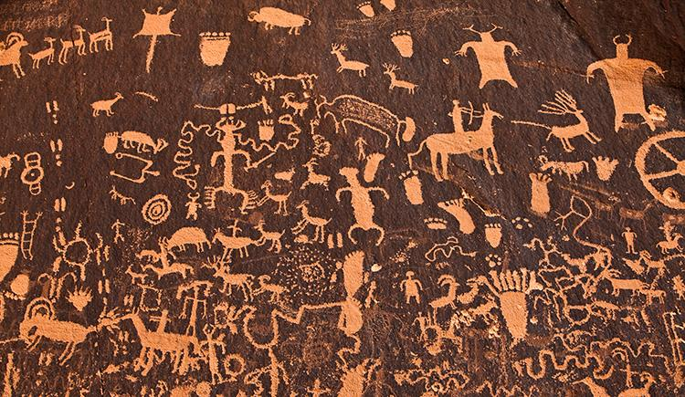 ancient cave art showing people and animals