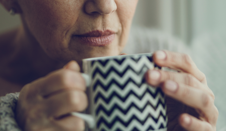 close up of older woman holding coffee mug to her nose