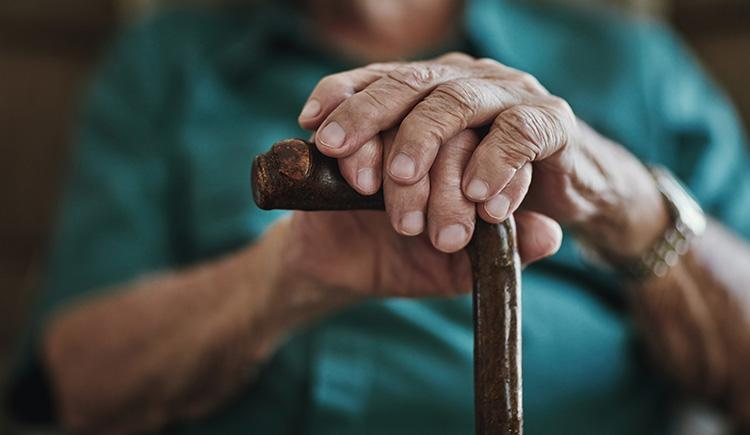 close up photo of a senior man's hands on a cane