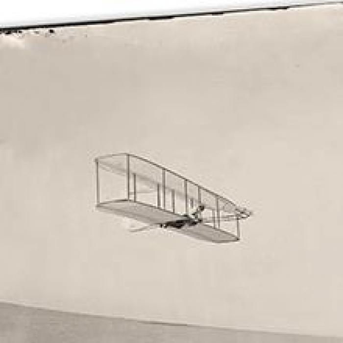 old photo of a biplane in flight
