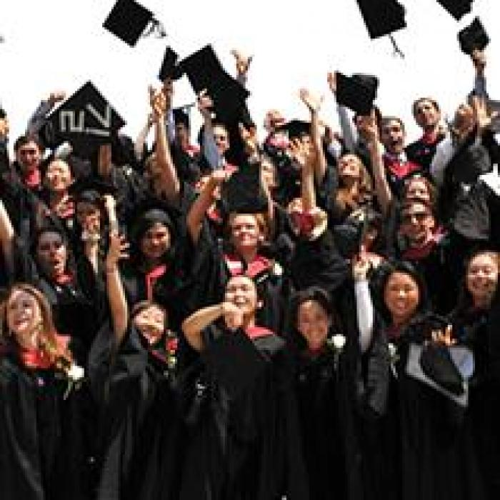 group of graduating student tossing their mortarboards into the air
