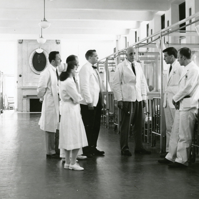 In this mid-twentieth century photo, William Bosworth Castle, MD 1921 (center) talks with medical staff and faculty in a ward at Boston City Hospital